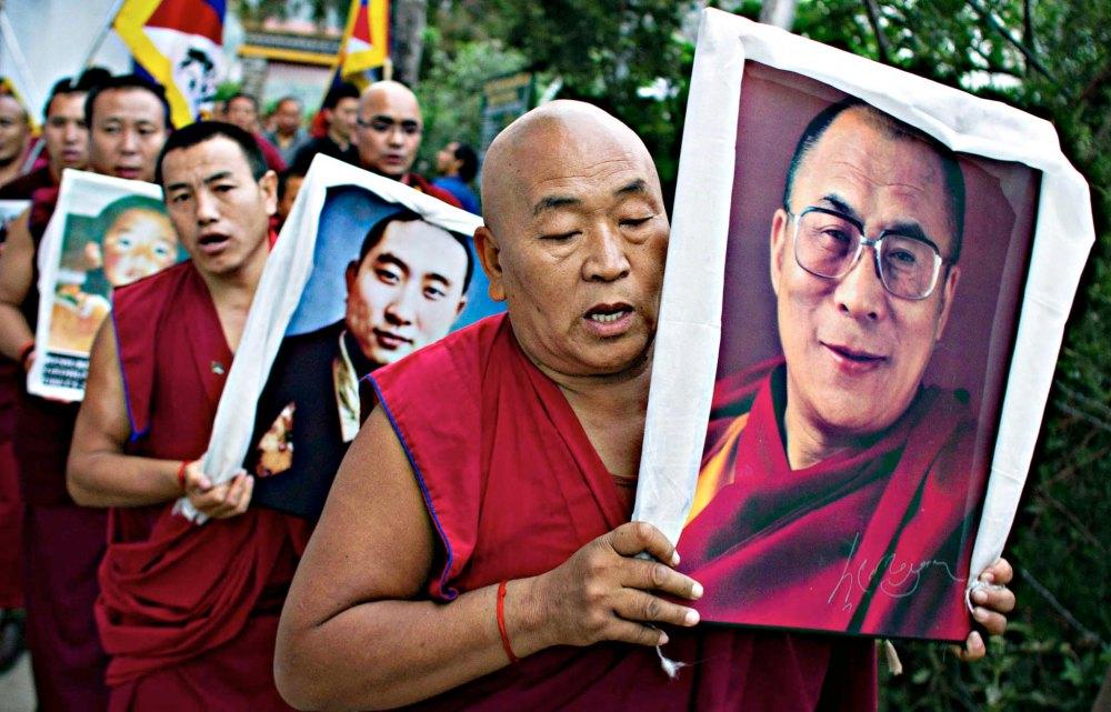 Un monaco buddista tibetano in esilio porta un ritratto del leader spirituale Dalai Lama durante una protesta a Dharmasala in India - © Ashwini Bhatia/AP . Fonte: http://blogs.ft.com/photo-diary/tag/dalai-lama/