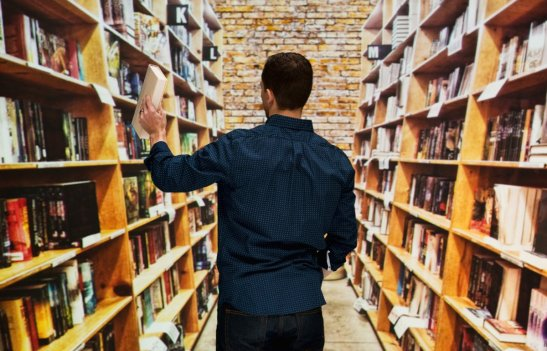 Ragazzo davanti a scaffali pieni di libri
